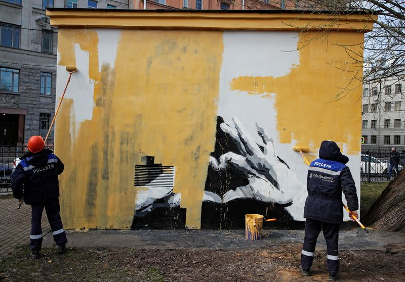 Workers paint over a graffiti depicting Alexei Navalny in Saint Petersburg