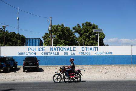 A man rides a bike in front of a main Haitian police station, where according to local media a group of foreign nationals including Americans armed with semi-automatic weapons were detained, after anti-government protests, in Port-au-Prince, Haiti, February 18, 2019. REUTERS/Ivan Alvarado
