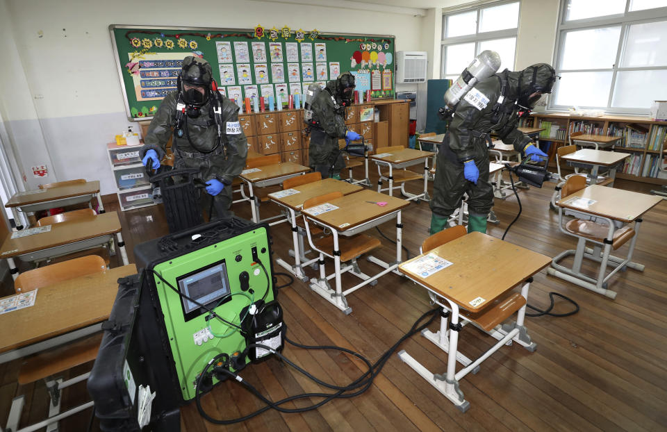 South Korean army soldiers spray disinfectant to help reduce the spread of the new coronavirus in a class at Cheondong elementary school in Daejeon, South Korea, Thursday, July 2, 2020. South Korea reported dozens of new cases as the virus continues to spread beyond the capital area and reach cities like Gwangju, which has shut schools and tightened social restrictions after dozens were found infected this week. (Kim Jun-beom/Yonhap via AP)