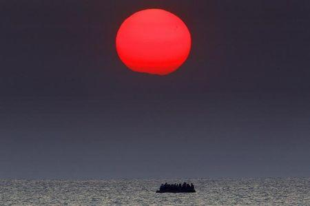 A red sun is seen over a dinghy overcrowded with Syrian refugees drifting in the Aegean sea between Turkey and Greece after its motor broke down off the Greek island of Kos, August 11, 2015.   REUTERS/Yannis Behrakis/File Photo