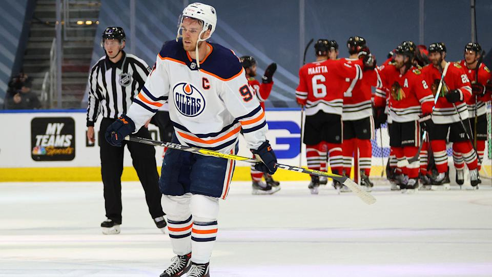 EDMONTON, ALBERTA - AUGUST 05: The Chicago Blackhawks congratulate one another on the ice as Connor McDavid #97 of the Edmonton Oilers looks on after Game Three of the Western Conference Qualification Round between the Edmonton Oilers and the Chicago Blackhawks at Rogers Place on August 05, 2020 in Edmonton, Alberta. The Blackhawks defeated the Oilers 4-3. (Photo by Dave Sandford/NHLI via Getty Images)