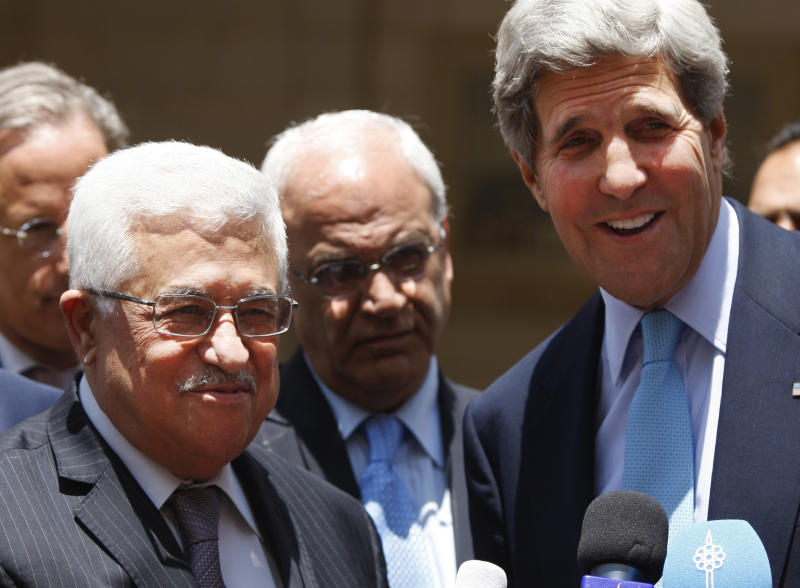 U.S. Secretary of State John Kerry, right, and Palestinian President Mahmoud Abbas brief the media after the meeting in the West Bank city of Ramallah, Sunday, June 30, 2013. Kerry continued his frenzied shuttle diplomacy Sunday to restart Mideast peace talks, but while Israel says it's ready to sit down, it showed no sign of bending to the Palestinians' long-standing demands for negotiating a two-state solution to the conflict. (AP Photo/Majdi Mohammed)