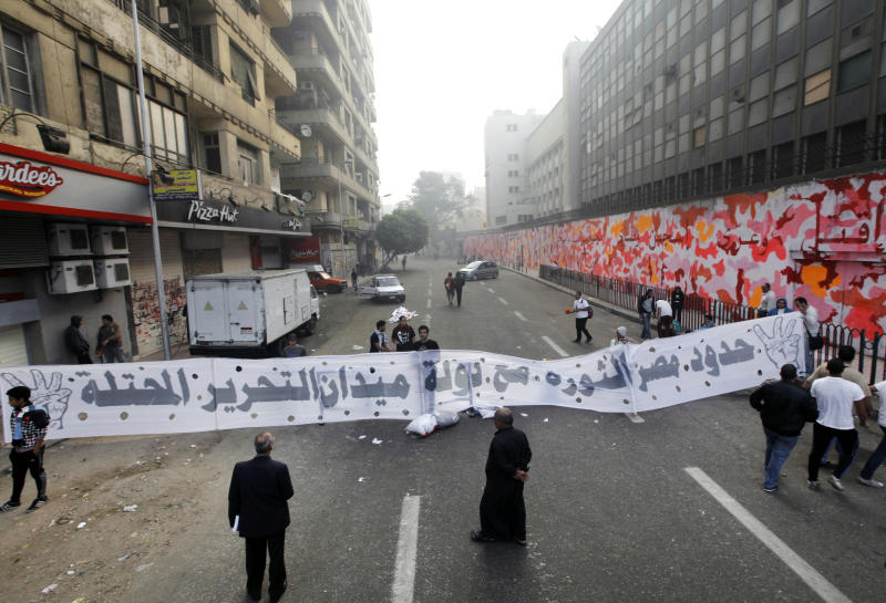 """Egyptians hold a large banner with Arabic that reads, """"the borders of Egypt's revolution, with the country of occupied Tahrir Square,"""" at the entrance of Mohammed Mahmoud street in Cairo, Egypt, Tuesday, Nov. 19, 2013. Egypt's revolutionary groups will mark Tuesday the second anniversary of some of the fiercest confrontations between Egyptian protesters and security forces in Mohammed Mahmoud street where scores had been killed. Rallies are also expected later in the day amid fears of more unrest and violence. (AP Photo/Amr Nabil)"""