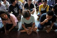 Thai youths with their calling numbers written on their arms sit as they wait for the start of a selection process to pick military recruits - through a lottery system - held at a temple grounds in Bangkok