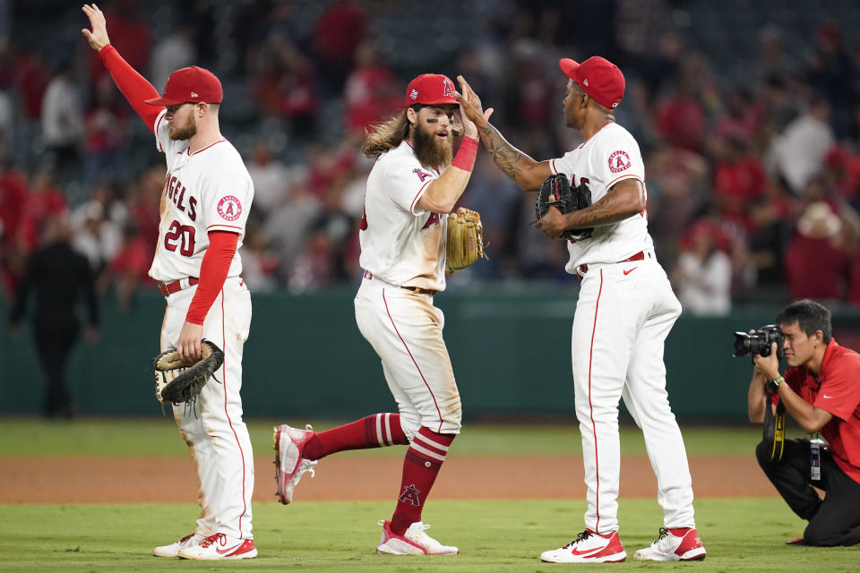 From left, Los Angeles Angels first baseman Jared Walsh (20), center fielder Brandon Marsh, and relief pitcher Raisel Iglesias celebrate after a 3-2 win over the Texas Rangers in a baseball game Friday, Sept. 3, 2021, in Anaheim, Calif. (AP Photo/Ashley Landis)
