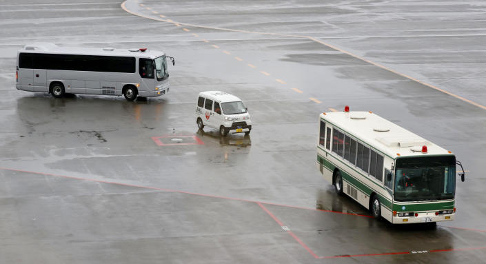 Vehicles carrying men who appear to be Michael Taylor and Peter Taylor, move on tarmac at Narita Airport in Narita, east of Tokyo, Tuesday, March 2, 2021. Two Americans suspected of helping former Nissan Chairman Carlos Ghosn skip bail and escape to Lebanon in December 2019 have been extradited to Japan. Taylor and his son Peter had been held in a suburban Boston jail since May. They were handed over to Japanese custody on Monday and were due to arrive in Tokyo on Tuesday. (Sadayuki Goto/Kyodo News via AP)