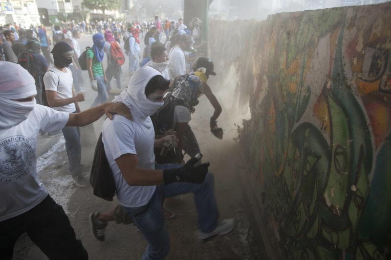 FILE - In this March 4, 2014 file photo, demonstrators destroy a wall in order to have more rocks to throw at the Bolivarian National Guard during anti-government protests in Caracas, Venezuela, one year after the death of Hugo Chavez. (AP Photo/Rodrigo Abd, File)