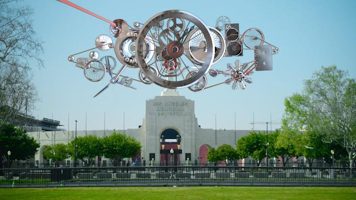 An explosion of clock gears appears to hover over the Los Angeles Memorial Coliseum