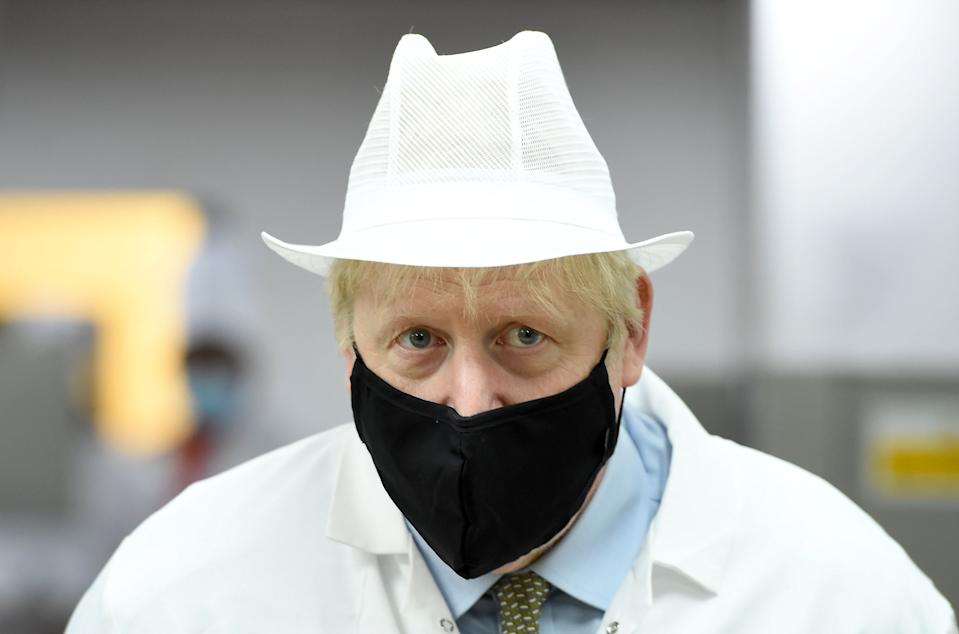 Britain's Prime Minister Boris Johnson, wearing a face mask or covering due to the COVID-19 pandemic, reacts during his visit to Royal Berkshire NHS Hospital in Reading, west of London on October 26, 2020, to mark the publication of a new review into hospital food. (Photo by Jeremy Selwyn / POOL / AFP) (Photo by JEREMY SELWYN/POOL/AFP via Getty Images)
