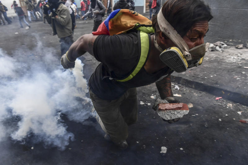 A demonstrator clashes with riot police as thousands march against Ecuadorean President Lenin Moreno's decision to slash fuel subsidies, in Quito on Oct. 9, 2019. (Photo: Martin Bernetti/AFP via Getty Images)