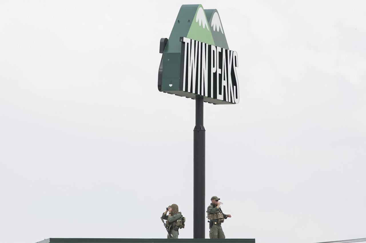 Police officers monitor the scene of a shooting from the roof of the Twin Peaks Restaurant in Waco, Texas May 18, 2015.  Police braced for retaliation attacks after 170 people were charged on Monday in connection with the shootout among motorcycle gangs a day earlier that left nine dead and 18 wounded at the Twin Peaks restaurant turned into a blood-soaked crime scene.  REUTERS/Laura Buckman      TPX IMAGES OF THE DAY