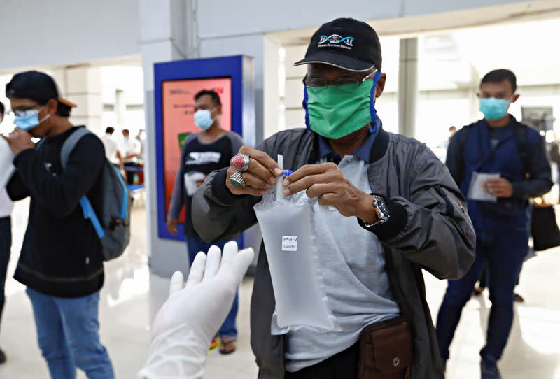 Commuters take their air-samples to be tested for the COVID-19, in Jakarta
