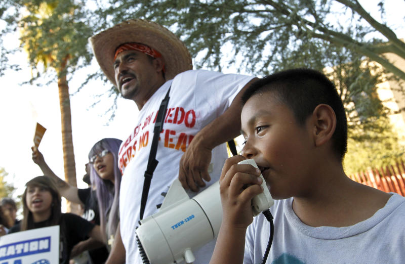 """Angel Ramirez, 9, right, leads protesters in protest chants as he gets some help from Geraldo Torrez, middle, as they join dozens who rally in front of U.S. Immigration and Customs Enforcement building, a day after a portion of Arizona's immigration law took effect, Wednesday, Sept. 19, 2012, in Phoenix. Civil rights activists contend will lead to systematic racial profiling, as the protesters chanted """"No papers, no fear.""""(AP Photo/Ross D. Franklin)"""