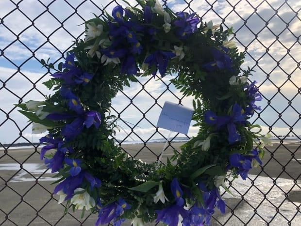 A memorial wreath pinned to the fence near the Cougar hangar in St. John's marks the anniversary of the Cougar Flight 491 crash.  (Jeremy Eaton/CBC - image credit)