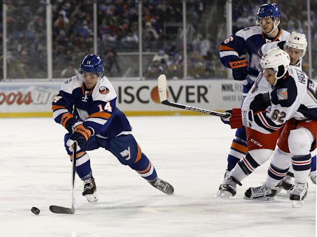 New York Islanders defenseman Thomas Hickey (14) skates with the puck in front of New York Rangers left wing Carl Hagelin (62) in the second period of an NHL hockey game at Yankee Stadium in New York, Wednesday, Jan. 29, 2014. (AP Photo/Kathy Willens)