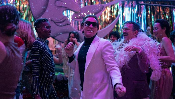 Ewan McGregor in a white suit dancing among people bathed in purple light in a still from Netflix's Halston.