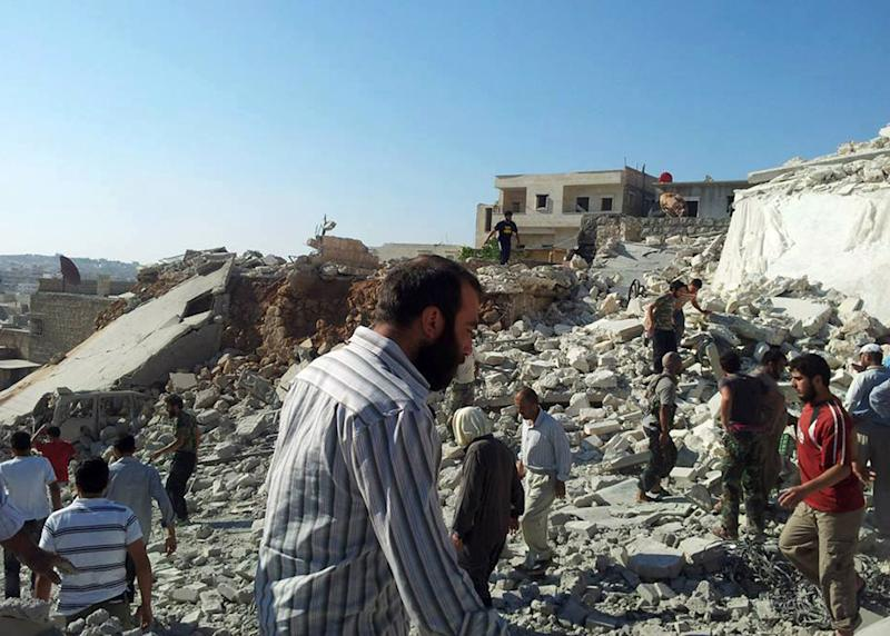 This citizen journalism image provided by The Syrian Revolution Against Bashar Assad which has been authenticated based on its contents and other AP reporting, shows Syrian citizens stand on rubble of destroyed houses that were damaged by Syrian forces airstrike, in the neighborhood of Darat Azza in Aleppo, Syria, Monday, June 17, 2013. The Britain-based Syrian Observatory for Human Rights said Monday that many soldiers died in the Sunday night attack in Mazzeh and many were wounded. The neighborhood houses several embassies and a military airport. (AP Photo/The Syrian Revolution Against Bashar Assad)