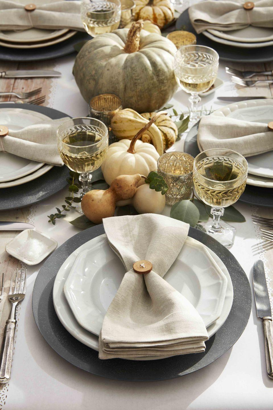 <p>This neutral toned place setting is just cute as a button! <strong><br></strong></p><p><strong>Make the napkin ring:</strong> Either buy wood buttons or drill small holes into small wood rounds. Thread holes with white twine and tie around napkins. </p>