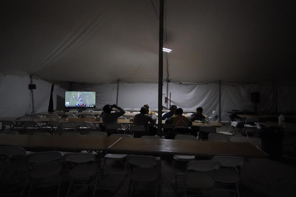 Workers watch TV and eat dinner in the cafeteria of a tent city for electrical workers in Amelia, La., Friday, Sept. 17, 2021. In one massive white tent, hundreds of cots are spread out; experienced workers bring their own inflatable mattresses. Another tent houses a cafeteria that serves hot breakfast starting about 5 a.m., dinner and boxed lunches that can be eaten out in the field. (AP Photo/Gerald Herbert)