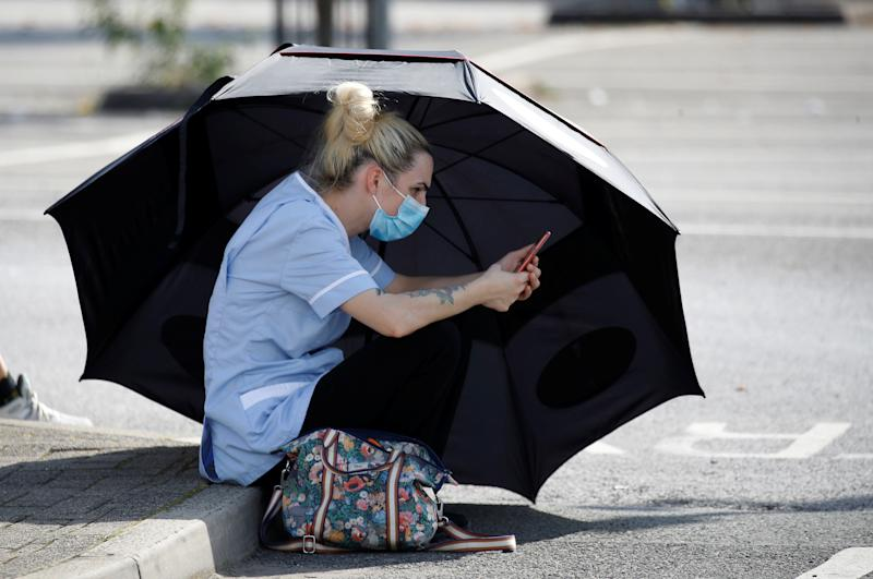 A woman uses an umbrella to shelter from the sun as she waits for a Coronavirus test outside a community centre in Bury, England following the outbreak of the coronavirus disease.