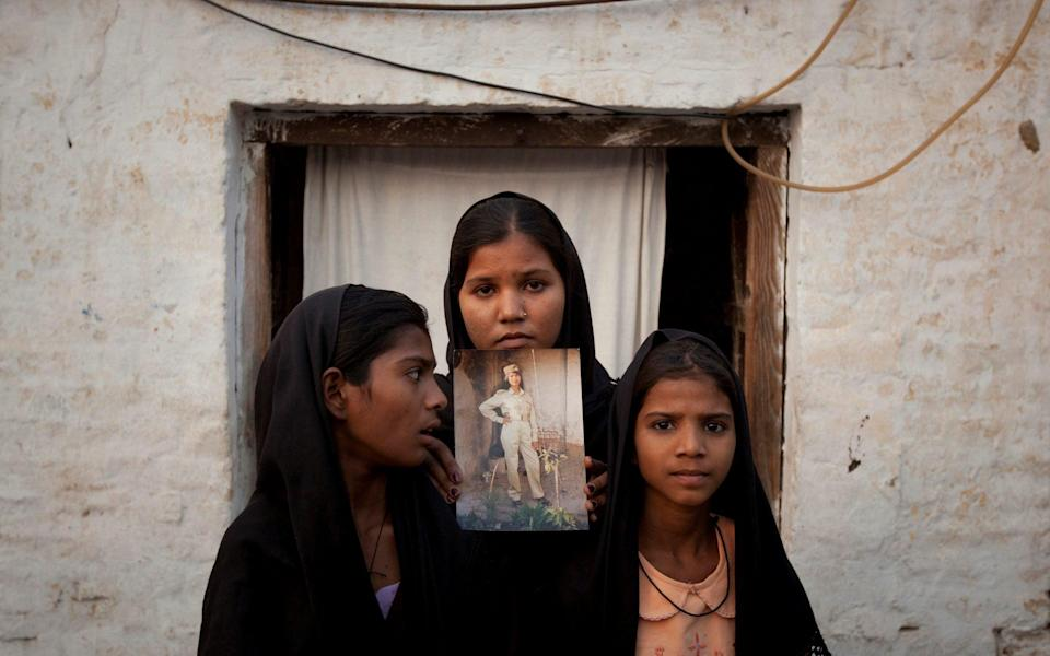 The daughters of Pakistani Christian woman Asia Bibi pose with an image of their mother while standing outside their residence in Sheikhupura located in Pakistan's Punjab Province - REUTERS