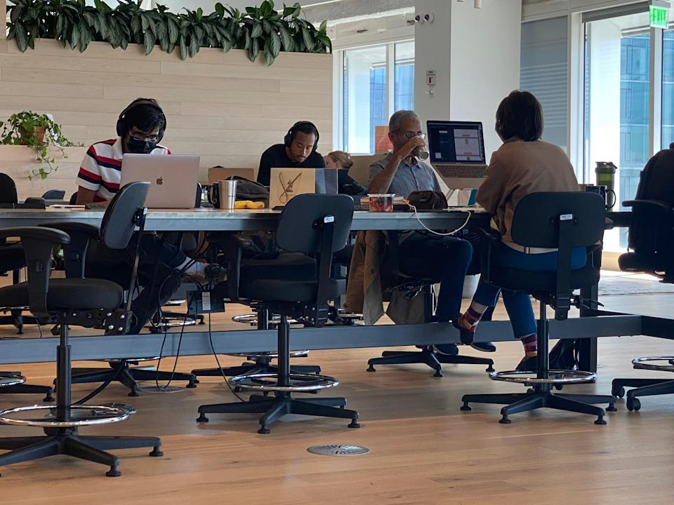 Tech workers, some wearing facemasks, work inside a downtown San Francisco coworking space. (Josh Marcus / The Independent)