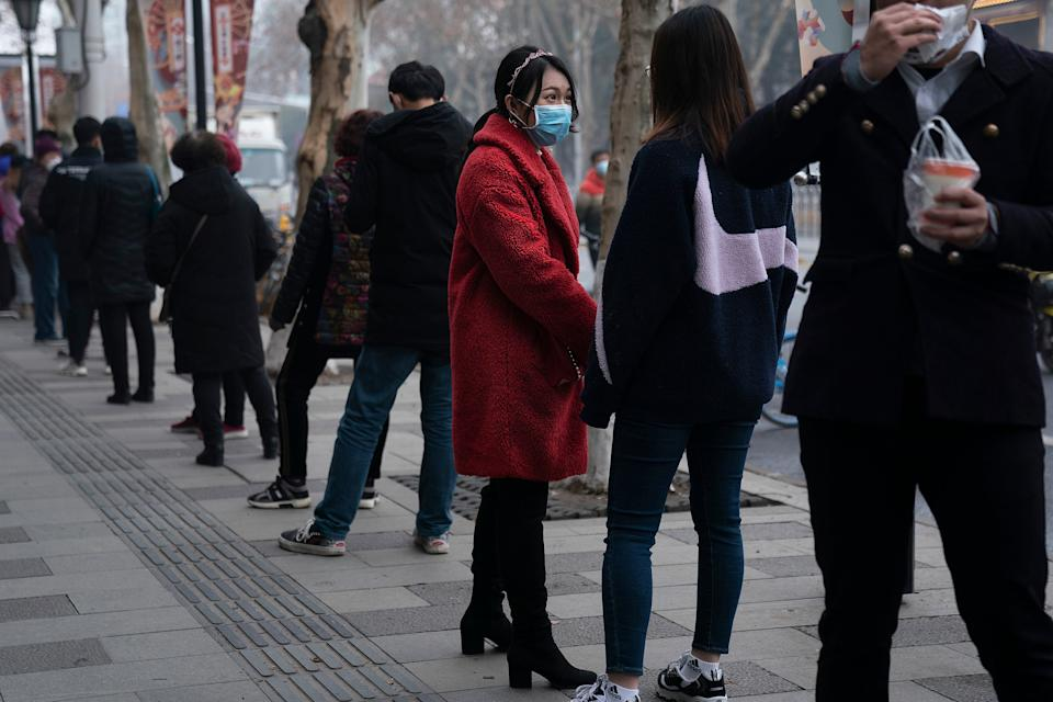 Residents wear masks while queuing to buy milky tea Getty