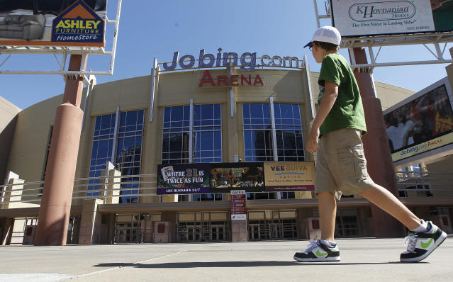 A lone pedestrian walks past Jobing.com Arena, Wednesday, June 13, 2012, in Glendale, Ariz., where the Phoenix Coyotes NHL hockey team plays home games. The conservative watchdog group Goldwater Institute has filed a lawsuit seeking to invalidate the Glendale City Council's vote to approve a lease agreement for Jobing.com Arena with a potential buyer of the Phoenix Coyotes. The lawsuit was filed today in Maricopa County Superior Court on behalf of Glendale taxpayers Ken Jones and Joe Cobb, claiming last week's vote violated a 2009 court order requiring Glendale to provide all documents in negotiations between the city and a prospective owner to Goldwater in a timely manner.(AP Photo/Ross D. Franklin)