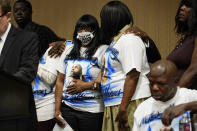 Robyn Williams, center right, sister of Byron Williams, comforts her niece Marcia Wells, center left, during a news conference Thursday, July 15, 2021, in Las Vegas. The family of 50-year-old Byron Williams whose death in Las Vegas police custody after a bicycle chase in 2019 was ruled a homicide is suing the city and four officers they accuse of wrongful death and civil rights violations. (AP Photo/John Locher)