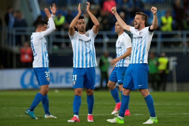 Malaga's players celebrates after winning 2-0 the Spanish league football match Malaga CF vs FC Barcelona at La Rosaleda stadium in Malaga on April 8, 2017