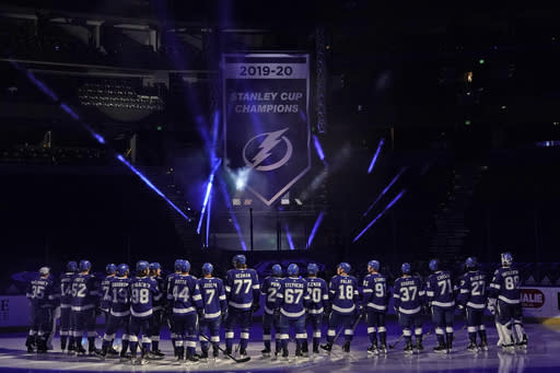Tampa Bay Lightning players look on as their 2019-2020 Stanley Cup Champions banner is revealed before an NHL hockey game against the Chicago Blackhawks Wednesday, Jan. 13, 2021, in Tampa, Fla. (AP Photo/Chris O'Meara)