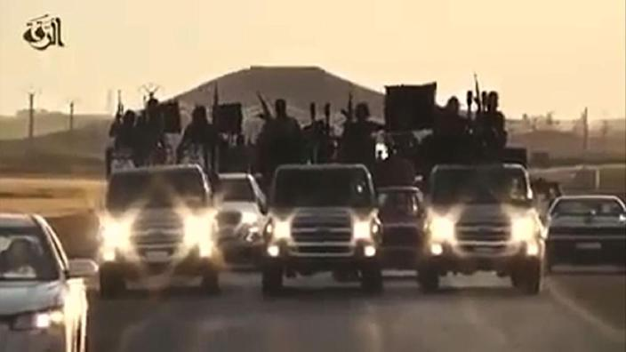An image grab taken from a video released by Islamic State group's official Al-Raqqa site via YouTube on September 23, 2014, allegedly shows Islamic State (IS) group recruits riding in armed trucks in an unknown location (AFP Photo/Ho)