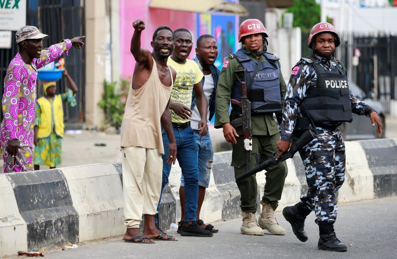 Men gesture as they stand near police officers along a street in Ikeja, in Lagos