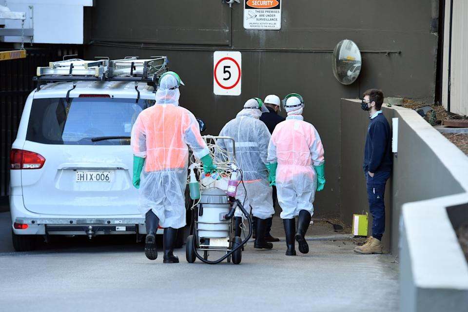 Cleaners in HAZMAT suits arrive at a locked downed apartment building on Devitt Street in the suburb of Blacktown in Sydney. Source: AAP