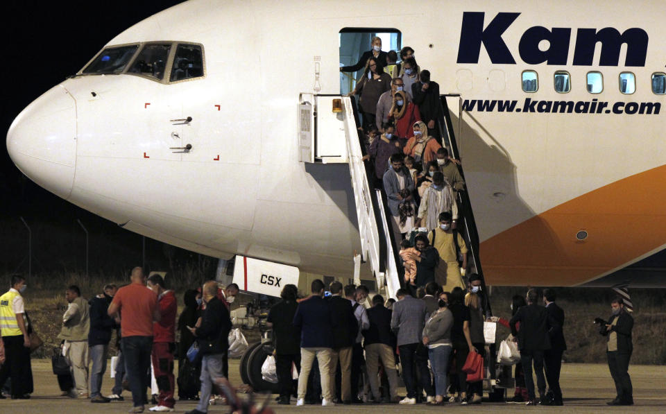 Afghan evacuees disembark a plane after landing at Skopje International Airport, North Macedonia, late Monday, Aug. 30, 2021. North Macedonia hosted the first group of about 150 Afghan evacuees who made it out of their country after days of chaos near the Kabul airport, following the takeover by the Taliban. (AP Photo/Boris Grdanoski)