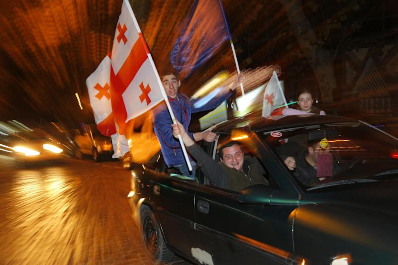 Georgian people drive around the city with national flags as they celebrate after the main independent exit poll announcement in Tbilisi, Georgia, Sunday, Oct. 27, 2013. Giorgi Margvelashvili, a former university rector with limited political experience, should get about 67 percent of the vote, the exit polls predicted. (AP Photo/Sergei Grits)