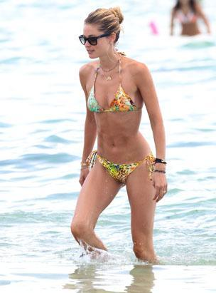 Victoria's Secret model Doutzen Kroes takes a swim in the ocean with husband DJ Sunnery James in Miami Beach, Fla., Aug. 17, 2012. The Dutch supermodel wore a citrus colored paisley triangle bikini with sunglasses