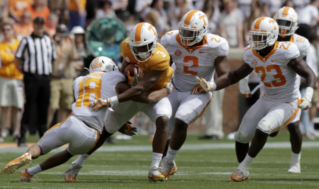 White team defensive back Nigel Warrior (18) wraps up Orange team running back Ty Chandler (3) during the Orange and White spring game at Neyland Stadium on Saturday, April 21, 2018 in Knoxville, Tenn. / (C.B. Schmelter /Chattanooga Times Free Press via AP)