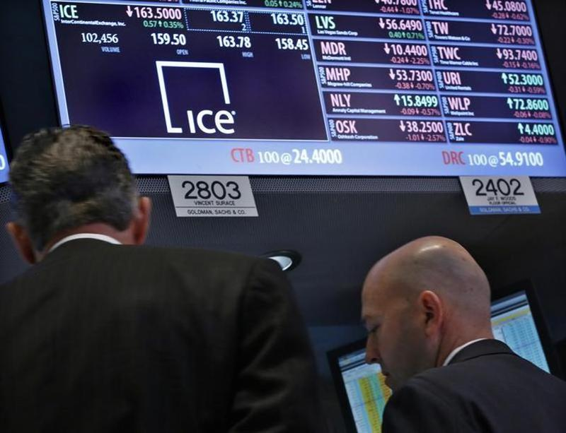 Specialist traders work at the booth that trades the stock for IntercontinentalExchange, on the floor at the New York Stock Exchange