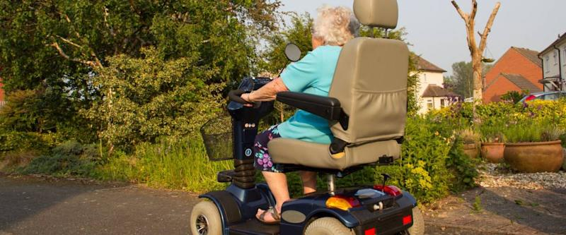 Old lady on her disabilty scooter enjoying the freedom to get around that it gives her.