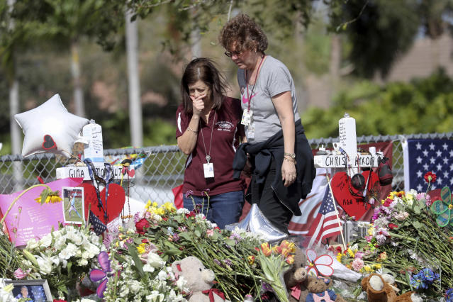 Two employees of Marjory Stoneman Douglas High School honor the dead. (Photo: Mike Stocker/South Florida Sun-Sentinel/AP)