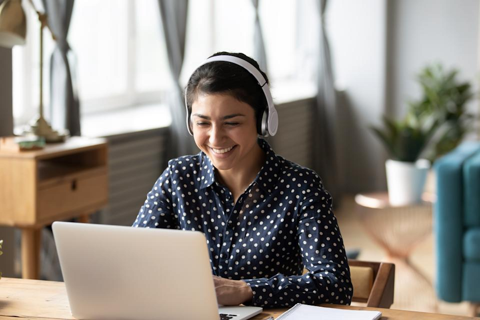Happy indian young girl student wear headphone watch webinar listen online course communicate by conference video call e learn language in app laugh study with teacher lesson look at laptop at home