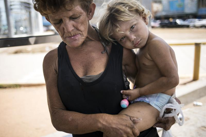 Homeless Carolina Duque holds her son Miguel Angel during a demonstration called by opposition politician Juan Guaido, who's urging masses into the streets to force President Nicolás Maduro from power, in Maracaibo, Venezuela, Saturday, Nov. 16, 2019. (AP Photo/Rodrigo Abd)