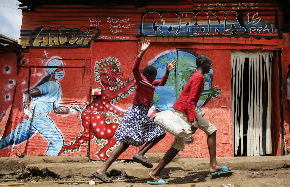 FILE - In this June 3, 2020, file photo, children run down a street past an informational mural warning people about the dangers of the new coronavirus, in the Kibera slum, or informal settlement, of Nairobi, Kenya. A new snapshot of the frantic global response to the coronavirus pandemic shows some of the world's largest government donors of humanitarian assistance are buckling under the strain and overall aid commitments have dropped by a third from the same period last year. (AP Photo/Brian Inganga, File)