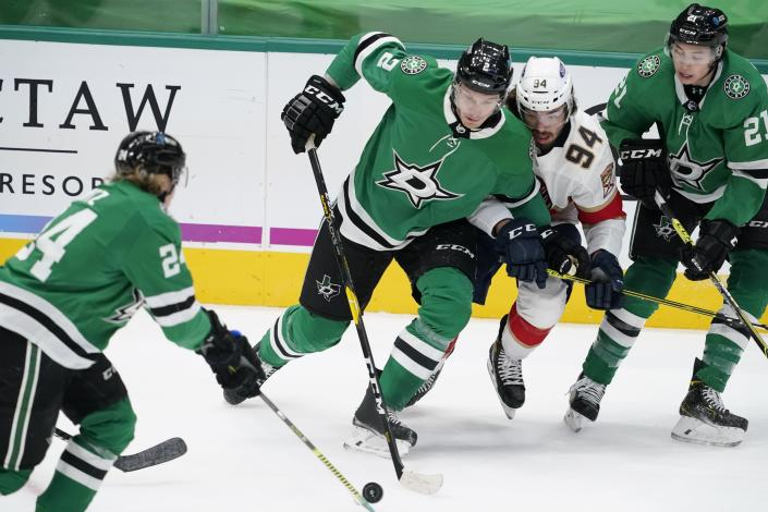 Dallas Stars' Roope Hintz (24), Jamie Oleksiak (2) and Jason Robertson (21) combine to control the puck in front of Florida Panthers left wing Ryan Lomberg (94) in the first period of an NHL hockey game in Dallas, Saturday, April 10, 2021. (AP Photo/Tony Gutierrez)