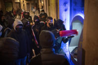 Demonstrators use an extinguisher to destroy a cash machine during a protest condemning the arrest of rap artist Pablo Hasél in Barcelona, Spain, Friday, Feb. 19, 2021. The imprisonment of a rap artist for his music praising terrorist violence and insulting the Spanish monarchy has set off a powder keg of pent-up rage this week in Spain. The arrest of Pablo Hasél has brought thousands to the streets for different reasons. The majority march under the banner of freedom of speech, but Hasél's lyrics also tap into a debate about the role of Spain's parliamentary monarchy after financial scandals involving the royal house. (AP Photo/Emilio Morenatti)