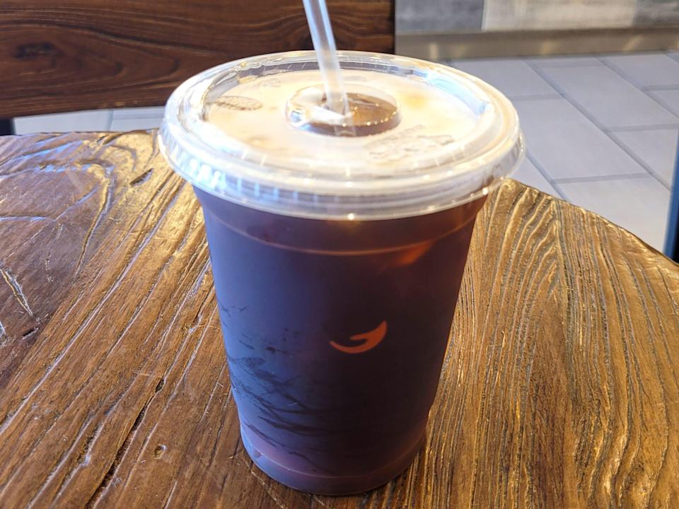 Cup of Gloria Jean's cold brew on a wooden table