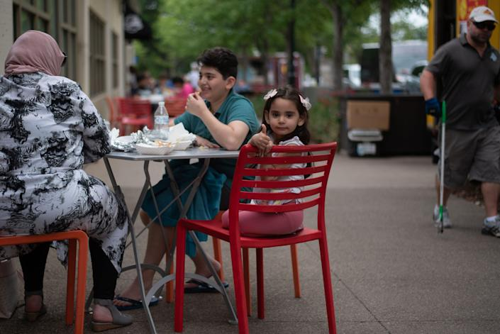 Leen Taleb, 3, eats lunch with her mother, Manar, and her brother, Tariq, on June 25, 2021, along Old Falls Street in Niagra Falls, N.Y. The family drove up from Ohio for a day trip.