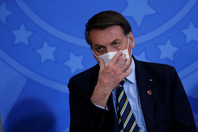 FILE PHOTO: Brazil's President Jair Bolsonaro adjusts his protective face mask during the inauguration ceremony of the new Communications Minister Fabio Faria (not pictured) at the Planalto Palace, in Brasilia