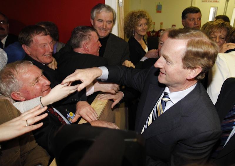 Fine Gael leader Enda Kenny, right, shakes hands with supporters in the ballot counting center at the Royal Castlebar theatre center, Castlebar, Ireland, Saturday, Feb. 26, 2011. Ireland's ruling Fianna Fail party faced its worst defeat in nearly 80 years, an exit poll predicted Saturday, as a tidal wave of voter anger swept the Fine Gael opposition into power and crushed the party that dragged Ireland to the edge of bankruptcy. (AP Photo/Peter Morrison)
